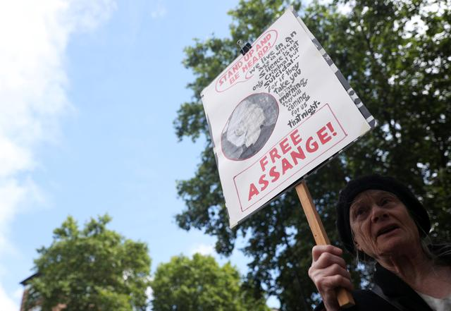 A demonstrator holding a placard protests outside of Westminster Magistrates Court, where a case hearing for U.S. extradition of Wikileaks founder Julian Assange is held, in London, Britain, June 14, 2019. REUTERS/Hannah Mckay - RC17C61BCDA0