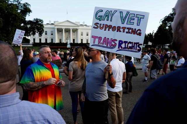 Demonstrators gather to protest U.S. President Donald Trump's announcement that he plans to reinstate a ban on transgender individuals from serving in any capacity in the U.S. military, at the White House in Washington, U.S. July 26, 2017.  REUTERS/Jonathan Ernst - RC12D641E1E0