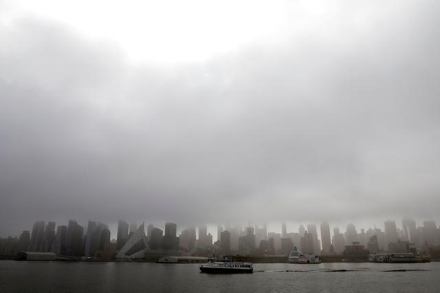 FILE PHOTO: A New York Waterway ferry boat crosses the Hudson River as heavy fog hangs over the Manhattan skyline in New York City, New York, U.S., May 2, 2019. REUTERS/Mike Segar/File Photo