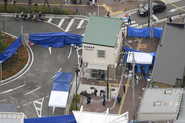 An aerial view shows police officers investigating the site where a police officer was found stabbed in front of a police box and the officer's gun, loaded with several bullets, was stolen, in Suita, Osaka prefecture, western Japan June 16, 2019, in this photo taken by Kyodo. Mandatory credit Kyodo/via REUTERS