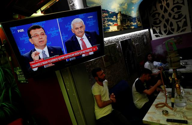 People watch a televised debate between Istanbul's mayoral candidates Ekrem Imamoglu of Republican People's Party (CHP) and Binali Yildirim of AK Party (AKP) at a cafe in central Istanbul, Turkey, June 16, 2019. REUTERS/Murad Sezer
