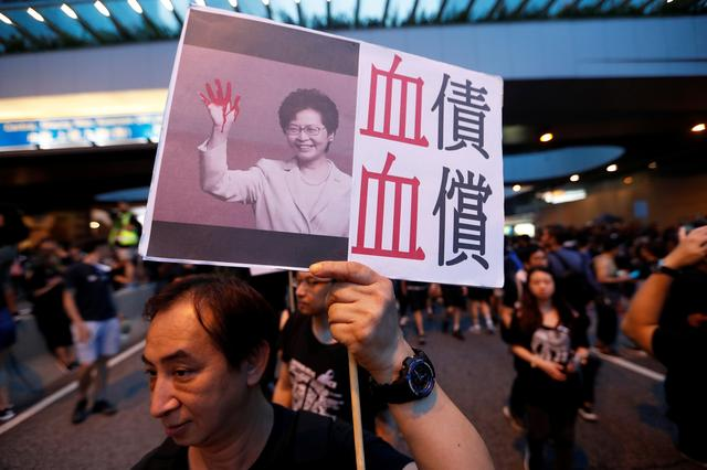 A protester holds a placard depicting Hong Kong Chief Executive Carrie Lam during a demonstration demanding Hong Kong's leaders to step down and withdraw the extradition bill, in Hong Kong, China, June 16, 2019. REUTERS/Jorge Silva