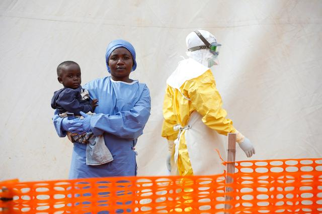 FILE PHOTO: Mwamini Kahindo, an Ebola survivor working as a caregiver to babies who are confirmed Ebola cases, holds an infant outside the red zone at the Ebola treatment centre in Butembo, Democratic Republic of Congo, March 25, 2019. REUTERS/Baz Ratner