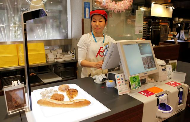 """A worker at the Andersen bakery uses a """"BakeryScan"""" checkout scanner at Ueno station in Tokyo, Japan, April 3, 2019. Picture taken on April 3, 2019.   REUTERS/Kaori Kaneko"""