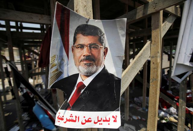 "FILE PHOTO: A poster of Egypt's President Mohamed Mursi reads, ""No substitute for the legitimacy"" is seen near members of the Muslim Brotherhood after night clashes with anti-Mursi around Cairo University and Nahdet Misr Square in Giza, on the outskirts of Cairo, Egypt July 3, 2013. REUTERS/Staff/File Photo"