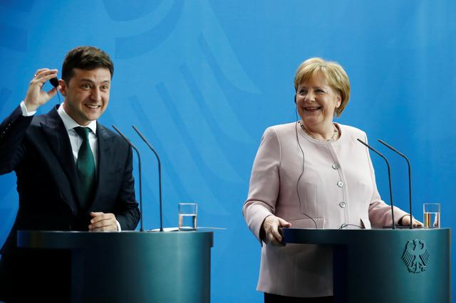 German Chancellor Angela Merkel and Ukrainian President Zelenskiy react during a news conference in Berlin, Germany, June 18, 2019. REUTERS/Hannibal Hanschke