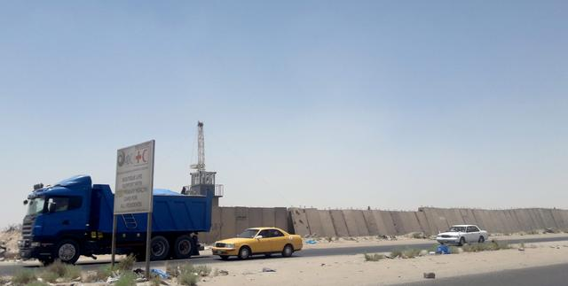 Vehicles drive past next to a security barrier of Zubair oilfield after a rocket landed at a residential and operations headquarters of several oil companies, at Burjesia area in Basra, Iraq June 19, 2019.  REUTERS/Essam Al-Sudani