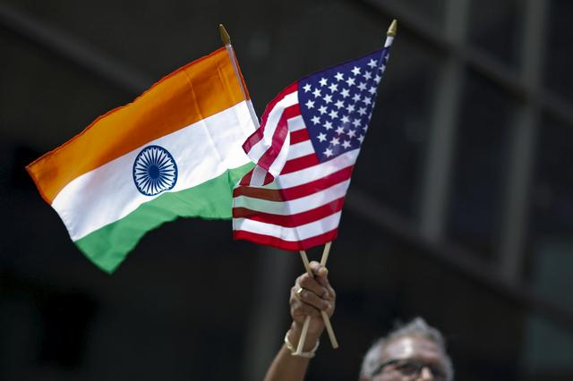 FILE PHOTO: A man holds the flags of India and the U.S. while people take part in the 35th India Day Parade in New York August 16, 2015. REUTERS/Eduardo Munoz/File Photo