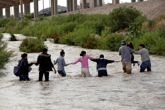 FILE PHOTO: Migrants from Central America form a human chain to cross the Rio Bravo river to enter illegally into the United States and turn themselves in to request asylum in El Paso, Texas, as seen from Ciudad Juarez, Mexico, June 11, 2019. REUTERS/Jose Luis Gonzalez/File Photo