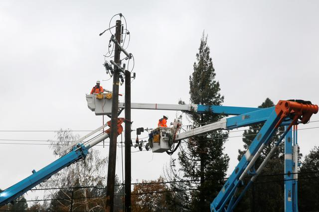 FILE PHOTO: PG&E crew work on power lines to repair damage caused by the Camp Fire in Paradise, California, U.S. November 21, 2018.  REUTERS/Elijah Nouvelage