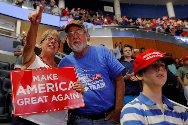 """John Lenges, 65, a resident of Pinellas County, who changed parties to vote Republican in 2016, and his sister Jeanne Coffin talk at the conclusion of U.S. President Donald Trump's re-election campaign kick off rally in Orlando, Florida, U.S., June 18, 2019.  I'd like to give him at least another four years."""" Before Trump announced his presidential bid, Lenges was a Democrat. He mostly tuned out politics and had never voted for a Republican president. """"It was a wakeup call,"""" he said. """"Our country needed a turn."""" Lenges' framed ticket to Trump's inauguration hangs on a home office wall once dedicated to NASCAR. REUTERS/Brian Snyder"""