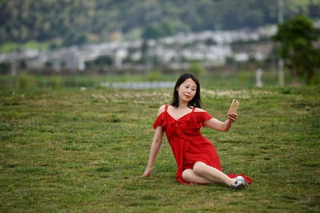 A woman takes selfies with a mobile phone near Erhai Lake in Dali Bai Autonomous Prefecture, Yunnan province, China June 15, 2019. REUTERS/Tingshu Wang
