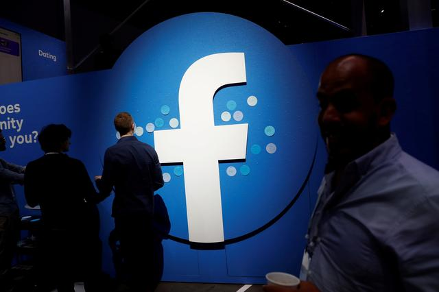 FILE PHOTO: Attendees walk past a Facebook logo during Facebook Inc's F8 developers conference in San Jose, California, United States, April 30, 2019.  REUTERS/Stephen Lam