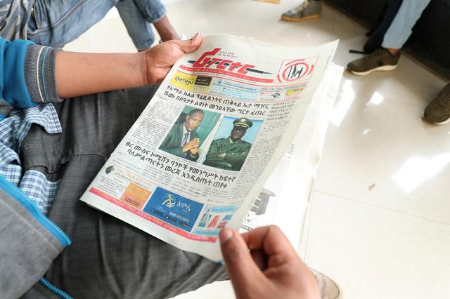 An Ethiopian man reads a newspaper with the pictures of Amhara state President Ambachew Mekonnen, killed in the region's main city Bahir Dar, and of Army Chief of Staff Seare Mekonnen, who was shot by his bodyguard, on a street in Addis Ababa, Ethiopia June 24, 2019. REUTERS/Tiksa Negeri