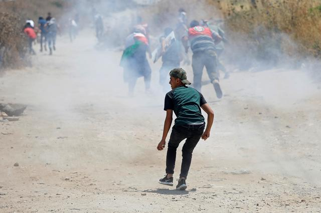 Palestinian demonstrators run for cover from tear gas fired by Israeli forces during a protest against Bahrain's workshop for U.S. peace plan, near the Jewish settlement of Beit El, in the Israeli-occupied West Bank June 24, 2019. REUTERS/Mohamad Torokman