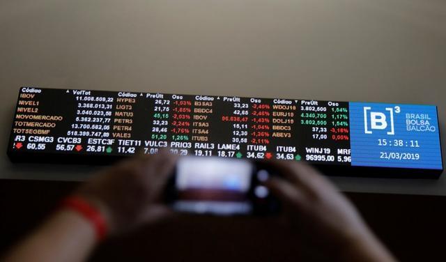 Foto de archivo. Un hombre toma una fotografía de una pantalla electrónica que muestra un gráfico de las recientes fluctuaciones de mercado en la bolsa de Valores de Sao Paulo. 21 de marzo de 2019. REUTERS/Nacho Doce.