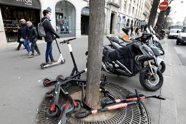 FILE PHOTO: A man rides an electric scooter on the sidewalk in Paris, France, March 27, 2019.  REUTERS/Charles Platiau/File Photo