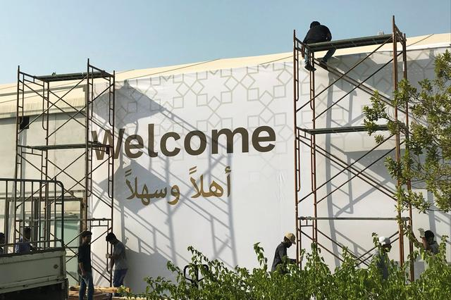 """Workers place a banner at the pavilion where the U.S. hosted event """"Peace to Prosperity"""" takes place outside Four Seasons Hotel in Manama, Bahrain June 24, 2019.  REUTERS/Matt Spetalnick"""