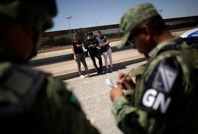 FILE PHOTO: Members of Mexico's National Guard detain Cuban migrants after they were trying to cross illegally the border between the U.S. and Mexico, in Ciudad Juarez, Mexico June 21, 2019. REUTERS/Jose Luis Gonzalez/File Photo