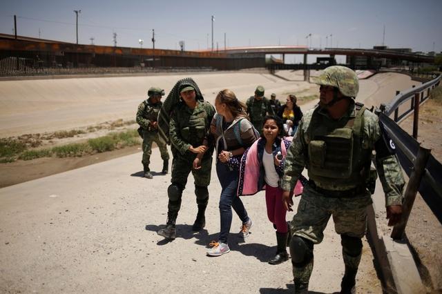Miembros de la Guardia Nacional de México escoltan a una mujer de Nicaragua y a su hija luego de detenerlas cuando intentaban cruzar ilegalmente la frontera entre Estados Unidos y México, en Ciudad Juárez, México. 21 de junio, 2019. REUTERS/Jose Luis Gonzalez
