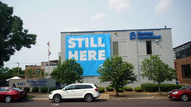 """A banner stating """"STILL HERE"""" hangs on the side of the Planned Parenthood Building after a judge granted a temporary restraining order on the closing of Missouri's sole remaining Planned Parenthood clinic in St. Louis, Missouri, U.S. May 31, 2019.  REUTERS/Lawrence Bryant"""