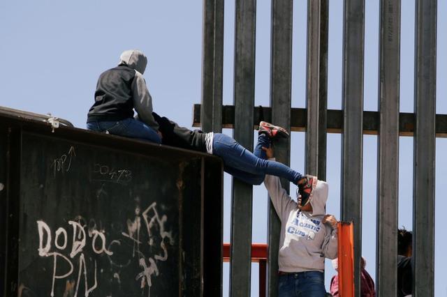 Inmigrantes saltan por un muro a Estados Unidos desde la frontera mexicana. Junio, 2019. REUTERS/Jose Luis Gonzalez