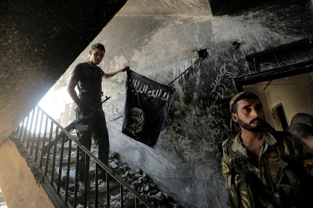 FILE PHOTO - A member of the Syrian Democratic Forces calls his comrades during the fighting with Islamic State fighters in Raqqa, Syria, August 14, 2017. REUTERS/Zohra Bensemra/File Photo