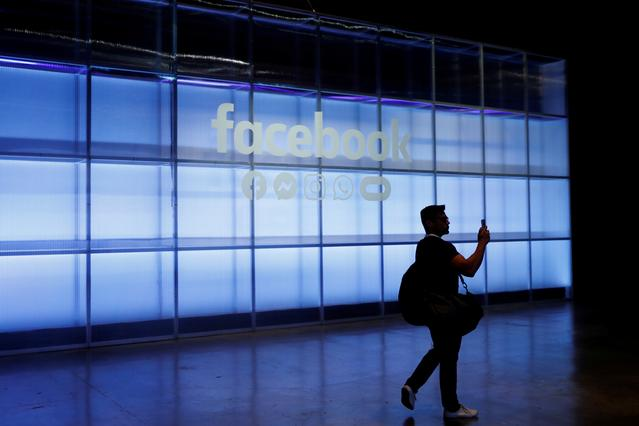 FILE PHOTO: An attendee takes a photograph of a sign during Facebook Inc's F8 developers conference in San Jose, California, U.S., April 30, 2019.  REUTERS/Stephen Lam/File Photo