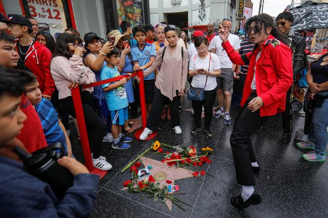 A Michael Jackson impersonator dances next to Michael Jackson's star on the Hollywood Walk of Fame ten years after the death of child star turned King of Pop in Los Angeles, California, U.S., June 25, 2019. REUTERS/Mike Blake
