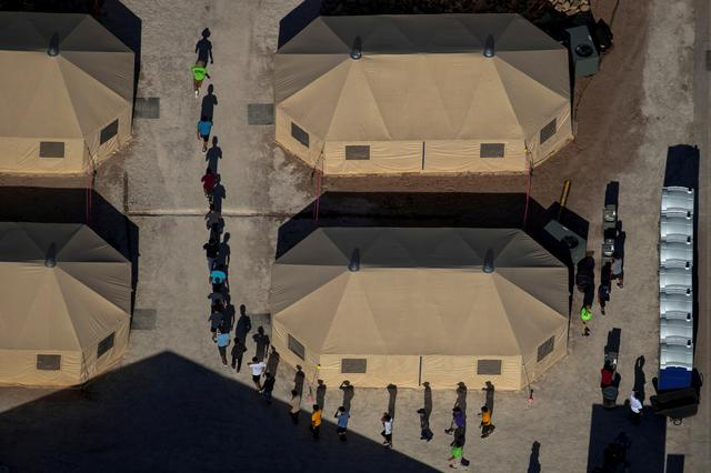 FILE PHOTO: Migrant children are led by staff in single file between tents at a detention facility next to the Mexican border in Tornillo, Texas  June 18, 2018.   REUTERS/Mike Blake/File Photo