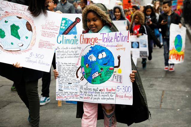 FILE PHOTO: Students hold banners and placards during a demonstration against climate change in New York, U.S., March 15, 2019. REUTERS/Shannon Stapleton