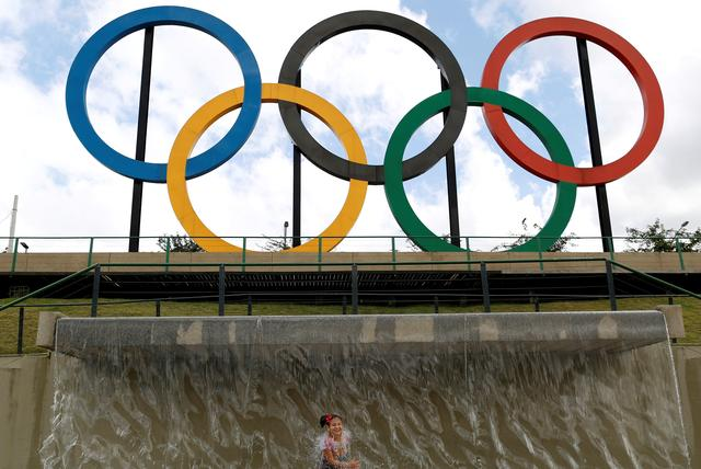 FILE PHOTO: A child plays in water near Olympic rings placed at Madureira Park ahead of the Rio 2016 Olympic Games in Rio de Janeiro, Brazil, July 17, 2016. REUTERS/Bruno Kelly