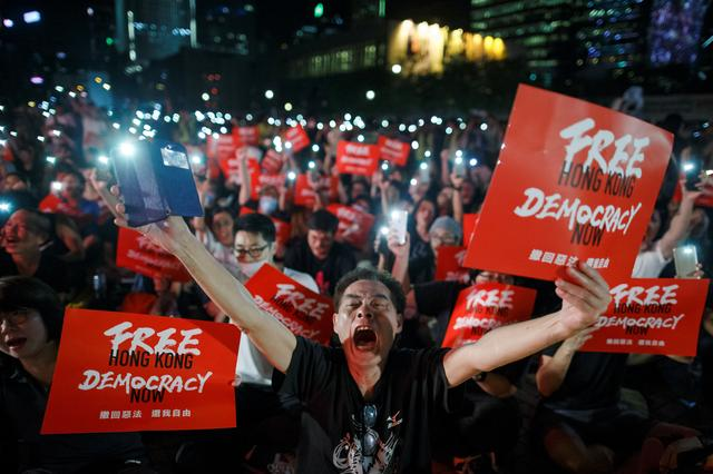 Demonstrators wave their smartphones and shout slogans during a rally ahead of the G20 summit, urging the international community to back their demands for the government to withdraw a the extradition bill in Hong Kong, China June 26, 2019.  REUTERS/Thomas Peter