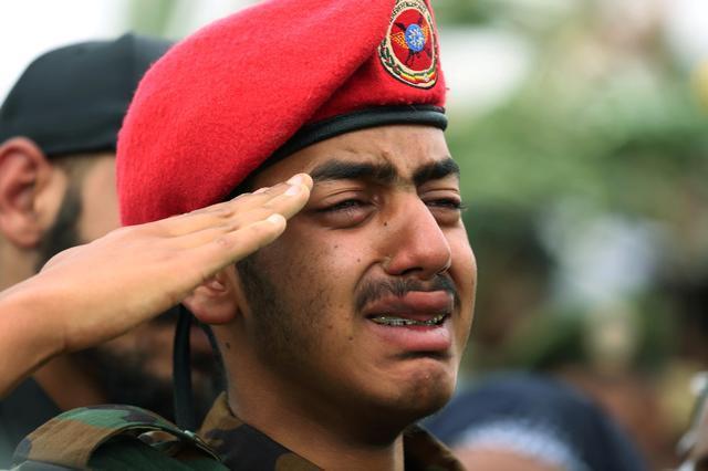An unidentified son of deceased Major General Gezayi Abera, who was killed by a bodyguard together with Ethiopian Army Chief of Staff Seare Mekonnen, salutes to his father's flag-draped coffin during the funeral ceremony, in Mekele, Tigray Region, Ethiopia June 26, 2019. REUTERS/Tiksa Negeri