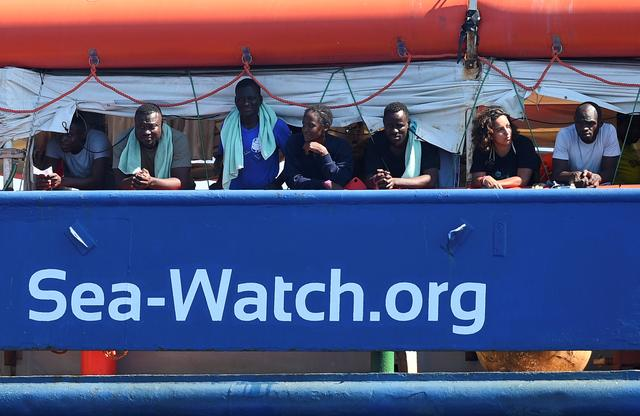 Migrants are seen at the search and rescue ship Sea-Watch 3, as it sails near the island of Lampedusa, Italy, June 26, 2019. REUTERS/Guglielmo Mangiapane
