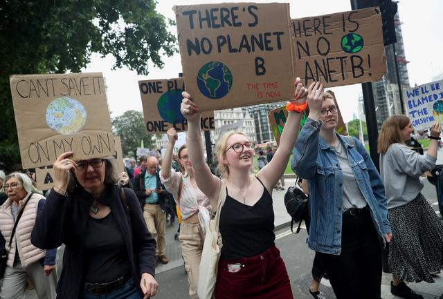 People carry placards as they attend a climate change demonstration in London, Britain, June 26, 2019. REUTERS/Hannah McKay