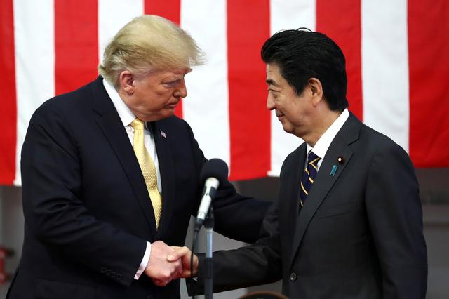 FILE PHOTO: U.S. President Donald Trump shakes hands with Japan's Prime Minister Shinzo Abe during delivering a speech to Japanese and U.S. troops as they aboard Japan Maritime Self-Defense Force's (JMSDF) helicopter carrier DDH-184 Kaga at JMSDF Yokosuka base in Yokosuka, south of Tokyo, Japan, May 28, 2019. REUTERS/Athit Perawongmetha/File Photo