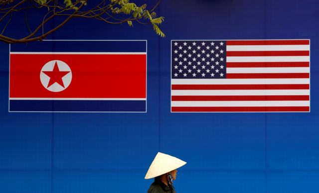 FILE PHOTO: A person walks past a banner showing North Korean and U.S. flags ahead of the North Korea-U.S. summit in Hanoi, Vietnam, February 25, 2019. REUTERS/Kim Kyung-Hoon