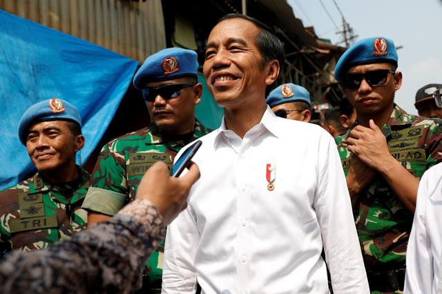 FILE PHOTO: Indonesia's Incumbent President Joko Widodo reacts after making a public address with his running mate Ma'ruf Amin, following the announcement of the last month's presidential election results at a rural area of Jakarta, Indonesia, May 21, 2019. REUTERS/Willy Kurniawan