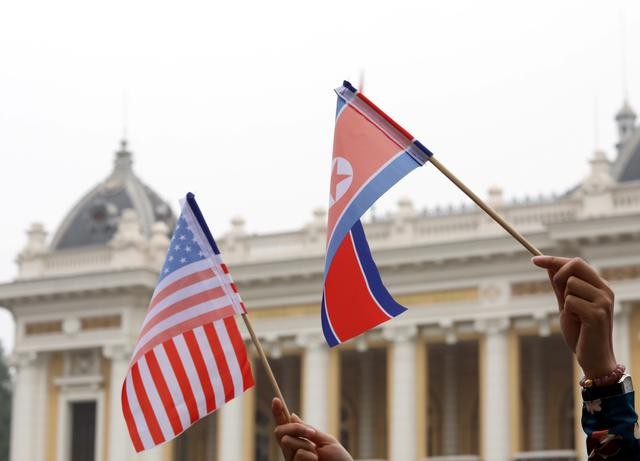 FILE PHOTO: Residents hold US and North Korean flags while they wait for motorcade of North Korea's leader Kim Jong Un en route to the Metropole Hotel for the second US- North Korea summit in Hanoi, Vietnam February 28, 2019. REUTERS/Kham