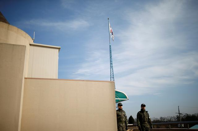 FILE PHOTO: South Korean flag flutters on the top of a 100-metre tower as soldiers stand guard on the rooftop of a village hall of the Tae Sung freedom village near the Military Demarcation Line (MDL), inside the demilitarised zone separating the two Koreas, in Paju, South Korea, November 22, 2016.  REUTERS/Kim Hong-Ji/File Photo