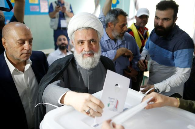 FILE PHOTO: Lebanon's Hezbollah deputy leader Sheikh Naim Qassem casts his vote as he stands next to Hezbollah parliament candidate Amin Sherri at a polling station during the parliamentary election, in Beirut, Lebanon, May 6, 2018. REUTERS/Mohamed Azakir