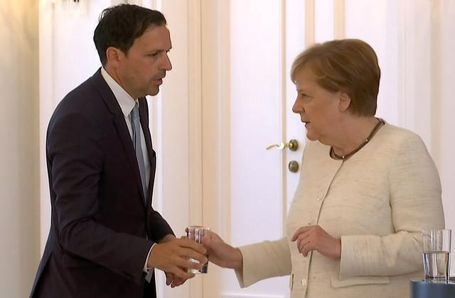 German Chancellor Angela Merkel receives water as she was seen shaking meeting President Frank-Walter Steinmeier in Berlin, Germany, June 27, 2019, her second shaking bout within two weeks.    REUTERS/Reuters TV