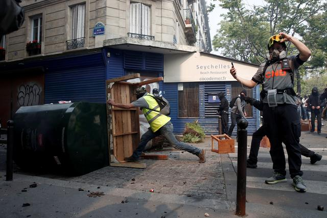 Masked protesters wearing yellow vests build barricades during clashes with riot police as part of the traditional May Day labour union march with French unions and yellow vests protesters in Paris, France, May 1, 2019.  REUTERS/Benoit Tessier