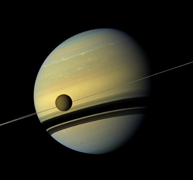 FILE PHOTO: Titan, Saturn's largest moon appears before the planet as it undergoes seasonal changes in this natural color view from NASA's Cassini spacecraft in this handout released by NASA August 29, 2012.    REUTERS/ NASA/JPL-Caltech/SSI