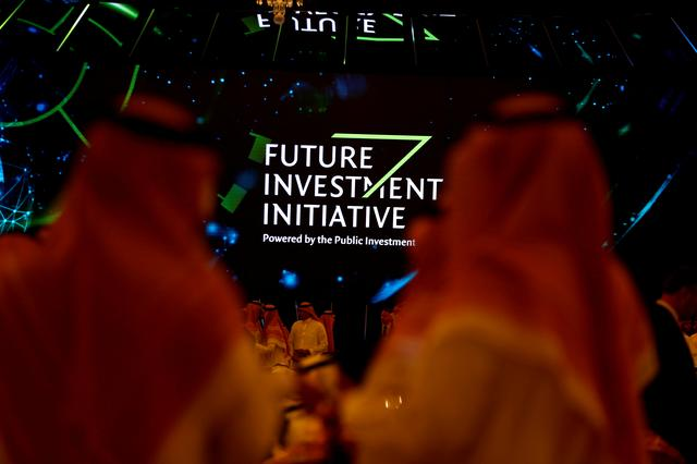 FILE PHOTO: Participants look at a sign of the Future Investment Initiative during the investment conference in Riyadh, Saudi Arabia October 23, 2018.  REUTERS/Faisal Al Nasser/File Photo