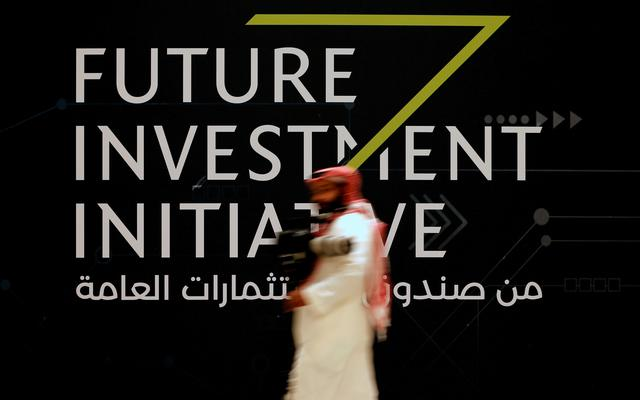 FILE PHOTO: A man walks past a sign at the Future Investment Initiative conference in Riyadh, Saudi Arabia October 24, 2017. REUTERS/Hamad I Mohammed/File Photo