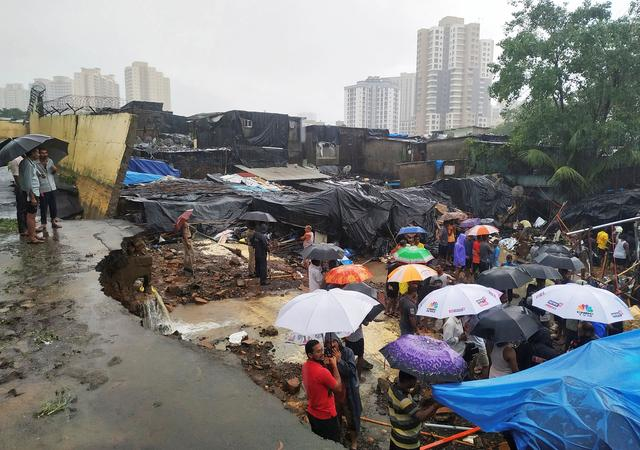 People stand among the debris after a wall collpased on hutments due to heavy rains in Mumbai, India July 2, 2019. REUTERS/Prashant Waydande
