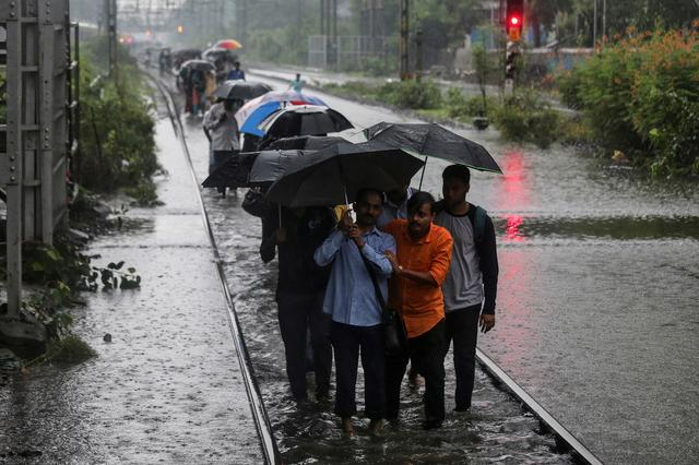 Commuters walk on waterlogged railway tracks after getting off a stalled train during heavy monsoon rains in Mumbai, India, July 2, 2019. REUTERS/Francis Mascarenhas