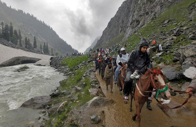 FILE PHOTO: Hindu pilgrims travel, either on ponies or on foot, along a track besides a glacier-fed stream during their annual pilgrimage to holy cave of Lord Shiva, in Pishutop, 114 km (71 miles) southeast of Srinagar June 25, 2012. REUTERS/Fayaz Kabli/File Photo
